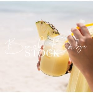 Hands holding a pineapple drink on the beach.
