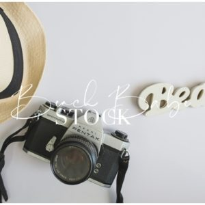 Styled Flatlay with sunhat, camera and beach sign