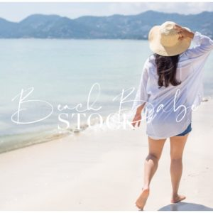 Woman Walking on the Beach with Sunhat